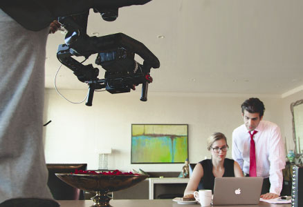 Man filming a couple of business people working at a laptop